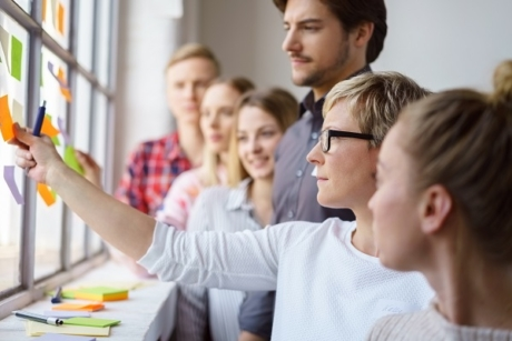 Ein Team diskutiert mit Post-its Ideen und klebt dies ans Fenster, Grundlagen des Projektmanagements